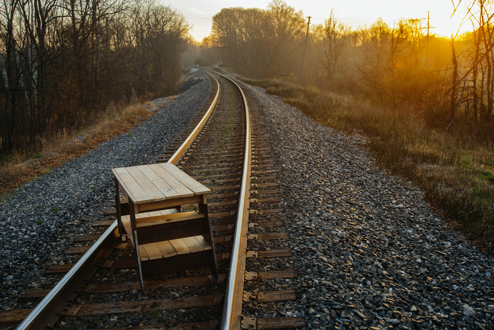 reclaimed table on train tracks at sunrise | the skulls