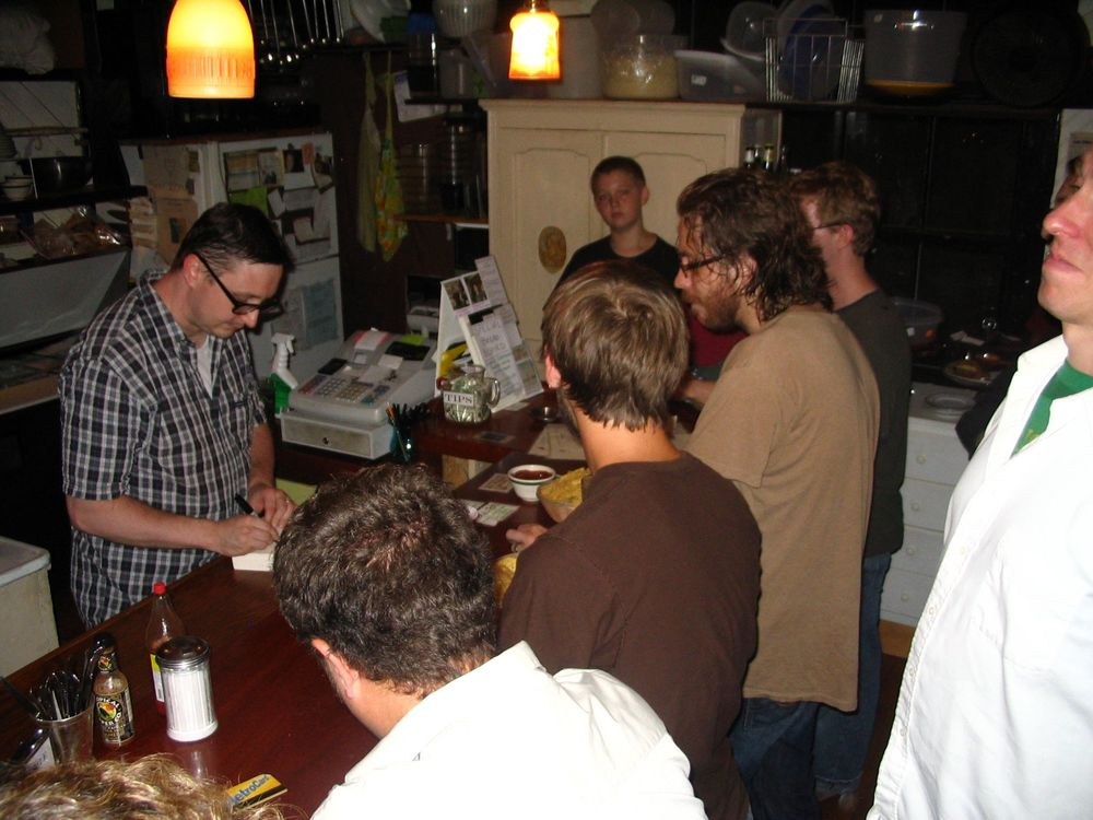 John Hodgman bartending on a very warm evening. Jonathan Coulton ordering from Hodgman on a very warm evening
