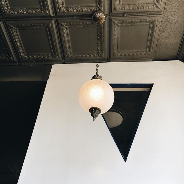 Old meet new. #ilikeitwhenthingslookpretty #remembertolookup #vsco #vscocam #cafedesign #tinceiling #pendant #window #scoutandco #winooski