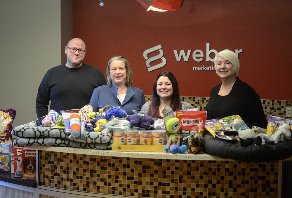 Warm beds, new toys, nutritious food, harnesses, leashes and other necessities collected during WMG's holiday food drive. (l-r) Joshua Law, Ruth Kapcia, Amy Morales, Barbara Glenn. Not pictured: Randy Schultz, Bruce Northey, Dana Northey, Ben Stangland, Mark Weber, Kory Davidson, Jamie Layton from Weber print parter  Imagine Visual Service .