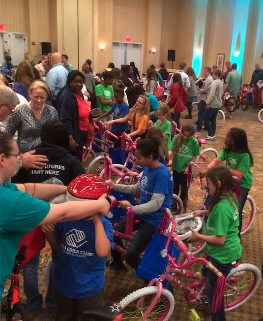 Staff present bikes they hand built to kids from the local Boys and Girls Club.