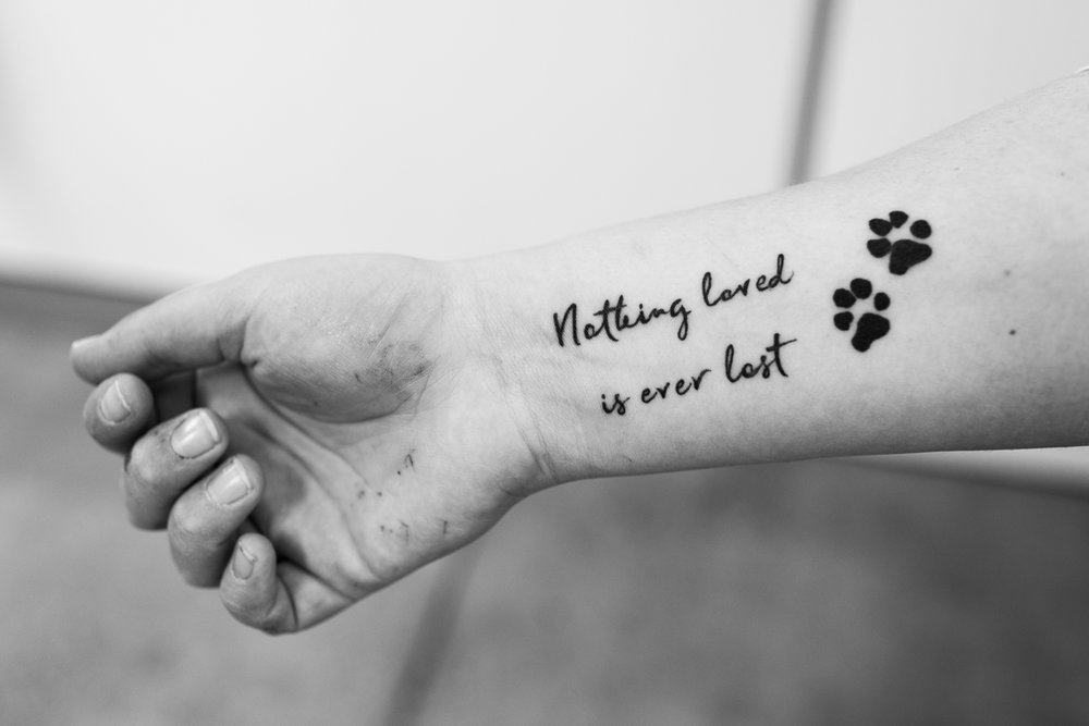 Nurse Kelsey Savage had this tattoo applied after losing one of her pet dogs, Hank. The paw prints are Hank's but the sentiment runs deeper.  27 July, 2018.