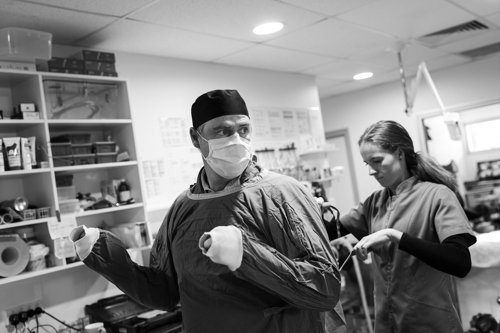 Dr Charlie Webb finishes gowns up, aided by Nurse Chelsea Rose.  16 March, 2018.