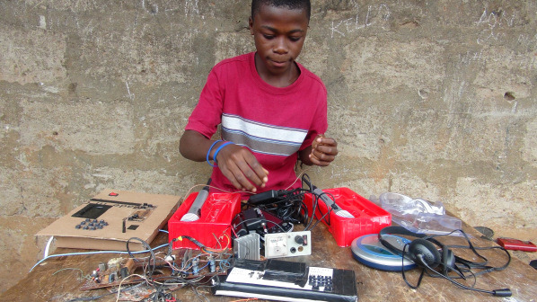 Kelvin Doe picks through electronics components to identify pieces to keep his homemade radio station is working order.