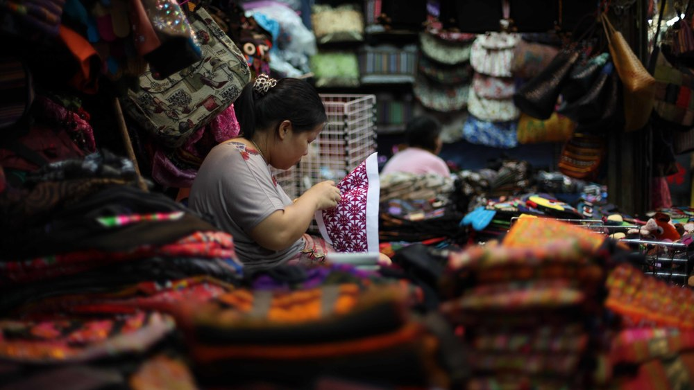A market trader adds touches to her textiles at the Chatuchak weekend market in Bangkok, Thailand.  Published   as artwork for a travel feature.