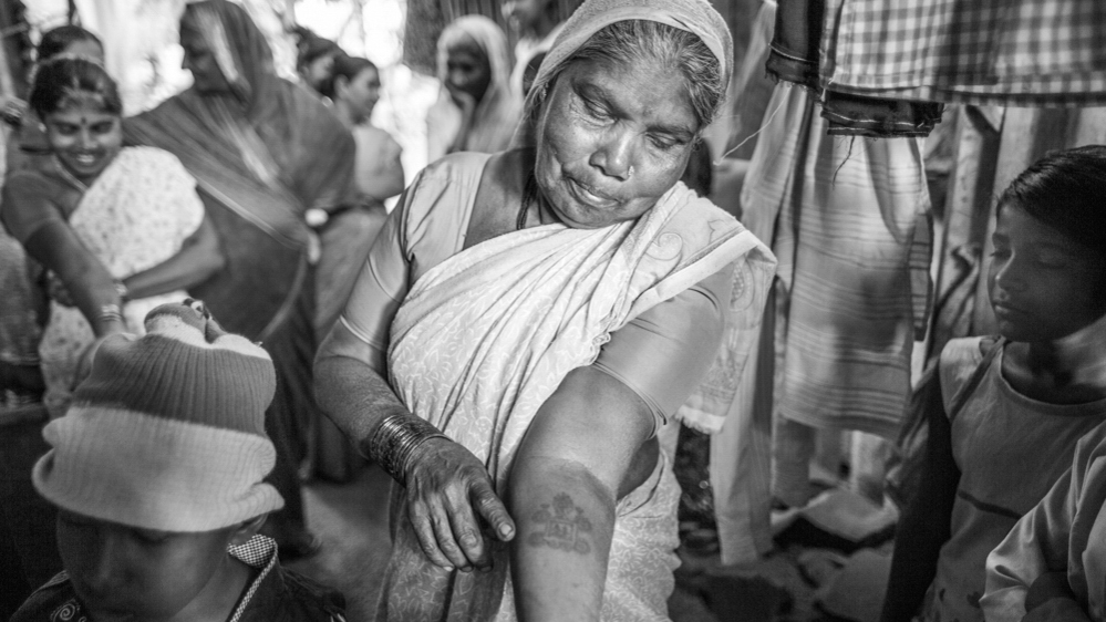 A community elder in Pune, India examines her tattoo.