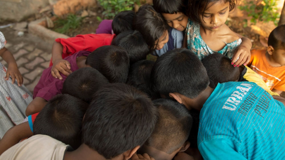 Creative Director Paul O'Driscoll on location in Pune, India. The children of the slum react to images of themselves, shown by Paul, who is crouched in the centre of the group.