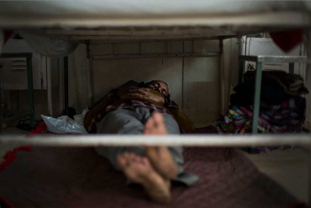 Badul Sekh naps under the hospital bed of his 10-year-old son. The polio ward at St. Stephen's Hospital, Delhi, is a family environment where relatives help nurses to feed, wash and comfort their loved ones.  Part of a photo essay for The Bill & Melinda Gates Foundation