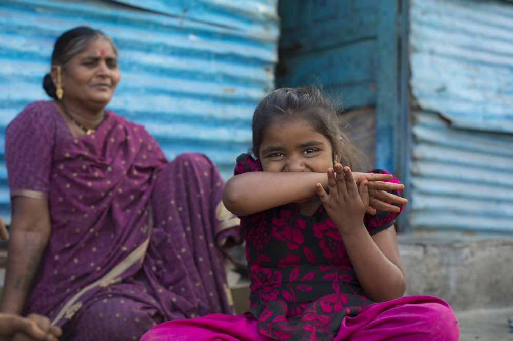 A girl in a slum area of Pune, India, is watched over by her mother. Parents are relieved that their children now have access to clean toilets provided by the Samagra sanitation initiative.  Part of photo essay produced for the Bill & Melinda Gates Foundation.