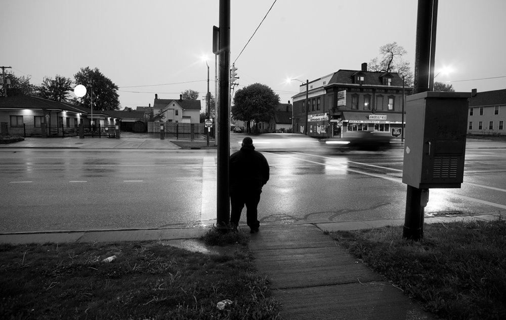 Shredrick Jordan waits in the predawn hours for the bus to take him to his job a MetroHealth.