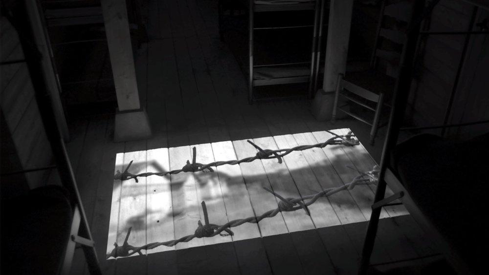 Projectie in een barak tussen stapelbedden
