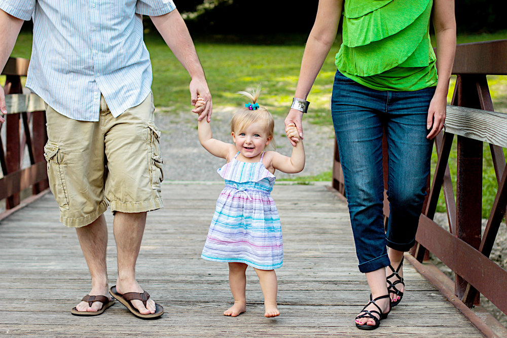 Mom and Dad walk with their little girl in a park during their family photography session in Kokomo, Indiana