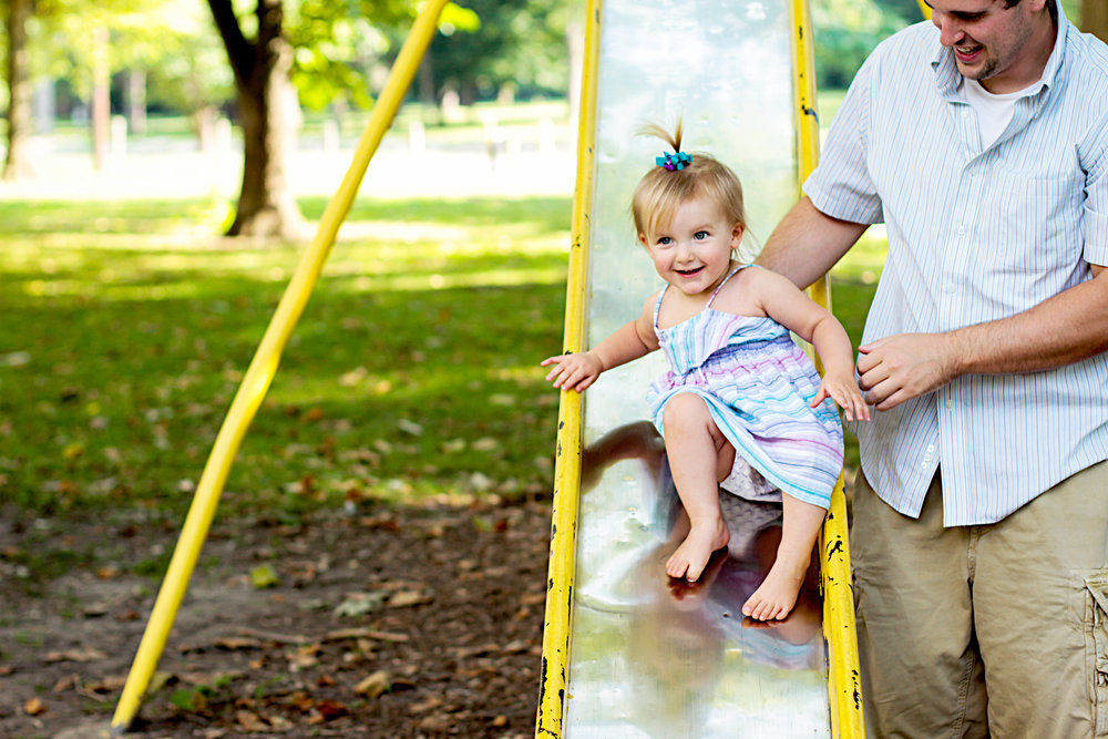 Maddy, with the help of her dad, slides down a slide at the park during her family photography session in Kokomo, Indiana.