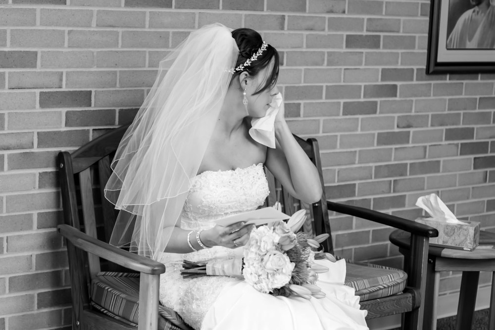 Fort Wayne Bride, Emily, cries as she reads a letter her parents wrote her on her wedding day.