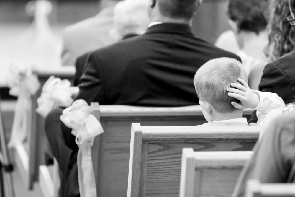 A little boy feels the fatique of a full Catholic Mass Wedding Ceremony in Fort Wayne Indiana.