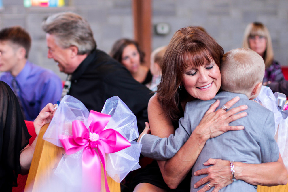 A aunt, who hasn't seen her newphew since the last family gathering, hugs him tight while his parents find their seats before a Wedding Ceremony they are attending in Dayton, Ohio