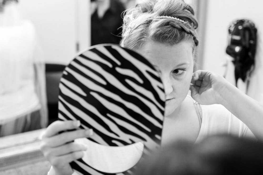 A Valparaiso Bride checks her hair in the mirror as she prepares for her summer wedding at the Red Barn Experience in Valparaiso, Indiana