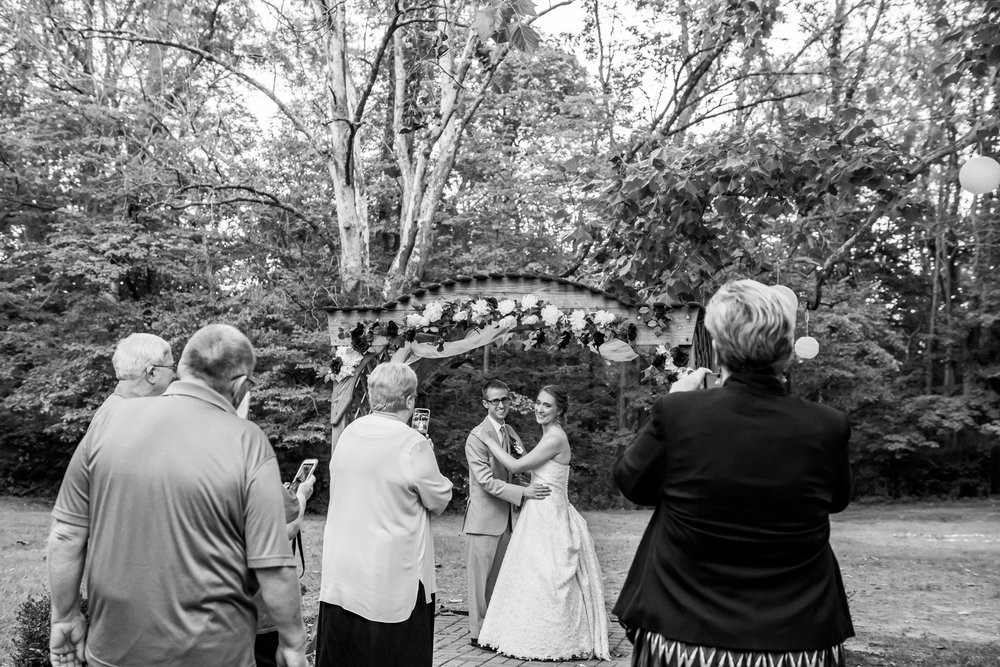 A bride and groom pose under an arch while family members take their wedding photos