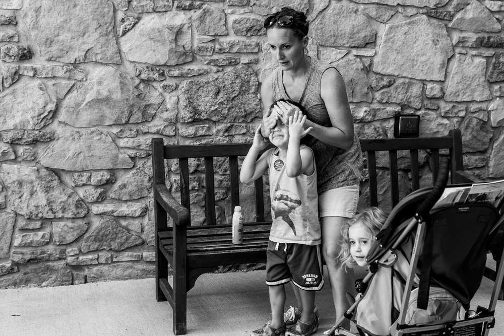 A mother, visiting a local outdoor museum with her kids, puts sunscreen on her oldest despite his protests. She knows that protection from the sun in in his best interest, even if he thinks it is literally the worst thing to ever happen to him. (Family Photography in Carmel, Indiana)