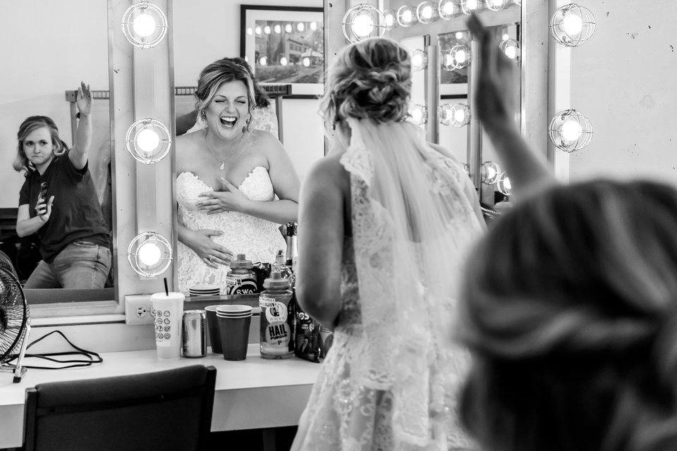 A bridesmaid dances in a mirror to make the bride laugh so that she doesn't cry and ruin her makup