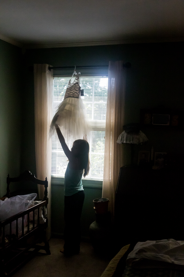 A flower girl reaches for her dress while its hanging in a window