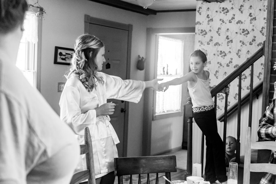 A little girl reaches out to a bride to encourage her to get ready faster