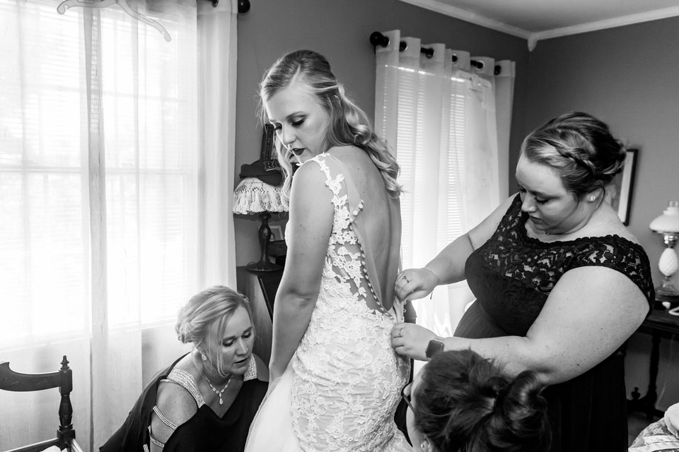 A bride puts on her wedding dress in her parents bedroom before heading to the ceremony