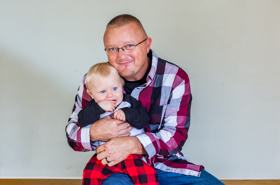 Cole sits with his dad for a photo during his one year photo session in Anderson, Indiana