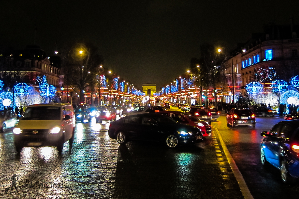 Even traffic on the Champs-Élysées looks cheerier with the street lined by lights and markets.