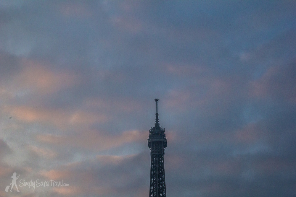 Top of Eiffel Tower with pink clouds of sunrise