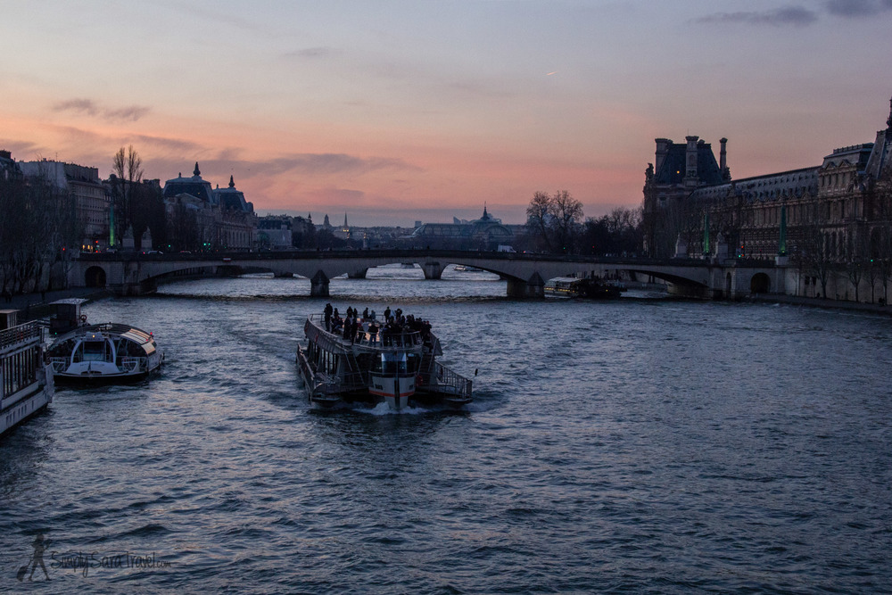 Winter sunset at the Seine with a passing boat by the Louvre, Paris, France