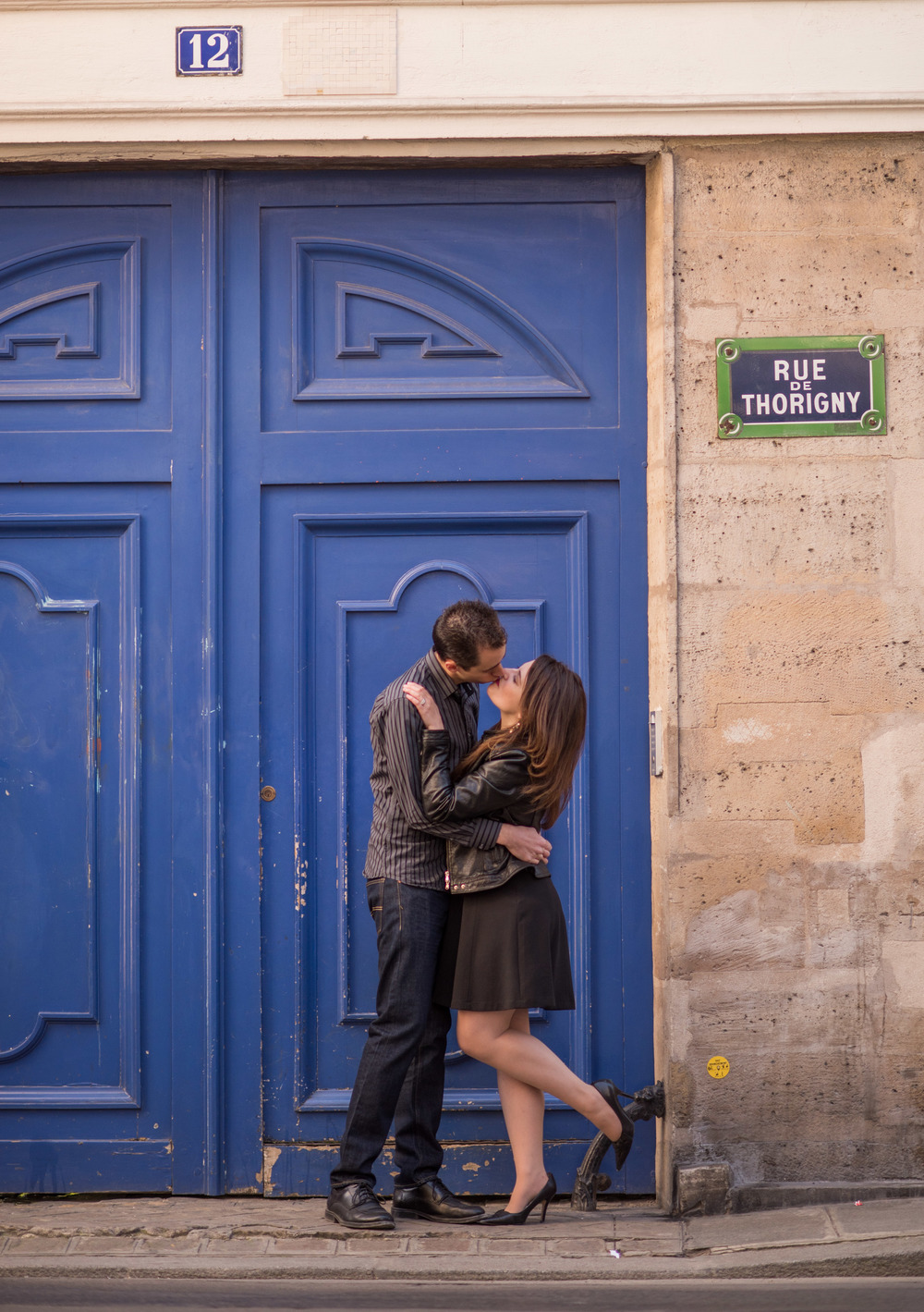 Kissing on rue de Thorigny with bright blue door, Marais, Paris, France, 75003