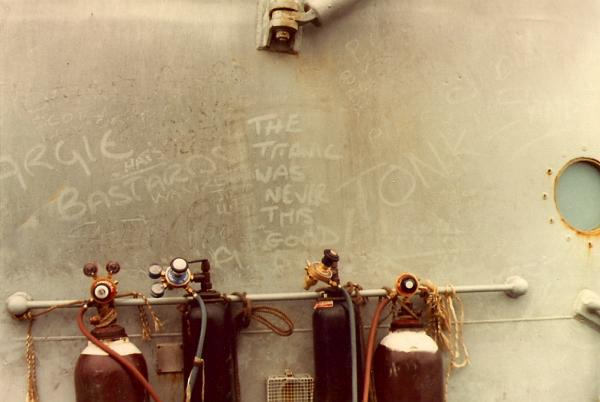 "Oxy-acetylene bottles on the foc'sle of Argonaut for damage repair. A fire broke out under a pile of welding bottles on the deck, but as the water started boiling-off the deck, we picked them up wearing firesuit gloves and threw them overboard. Amongst the irreverent comments on the soot covered bulkhead were the words ""The Titanic was never this good""."