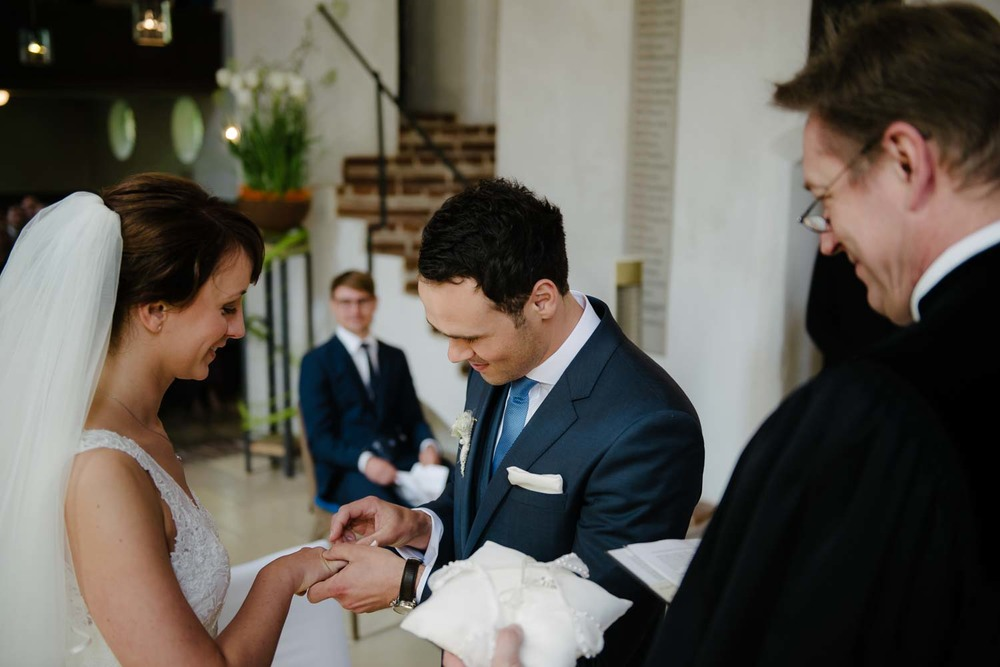 Ringübergabe Bräutigam steckt Braut den Hochzeitsring an. kirchliche Trauung Hochzeit Rostocker Fotograf in Augsburg