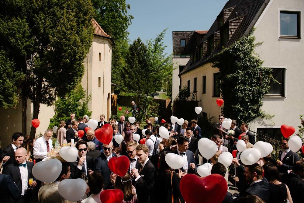 Hochzeitsgesellschaft mit roten und weissen Luftballons Empfang Hochzeit Rostocker Fotograf in Augsburg