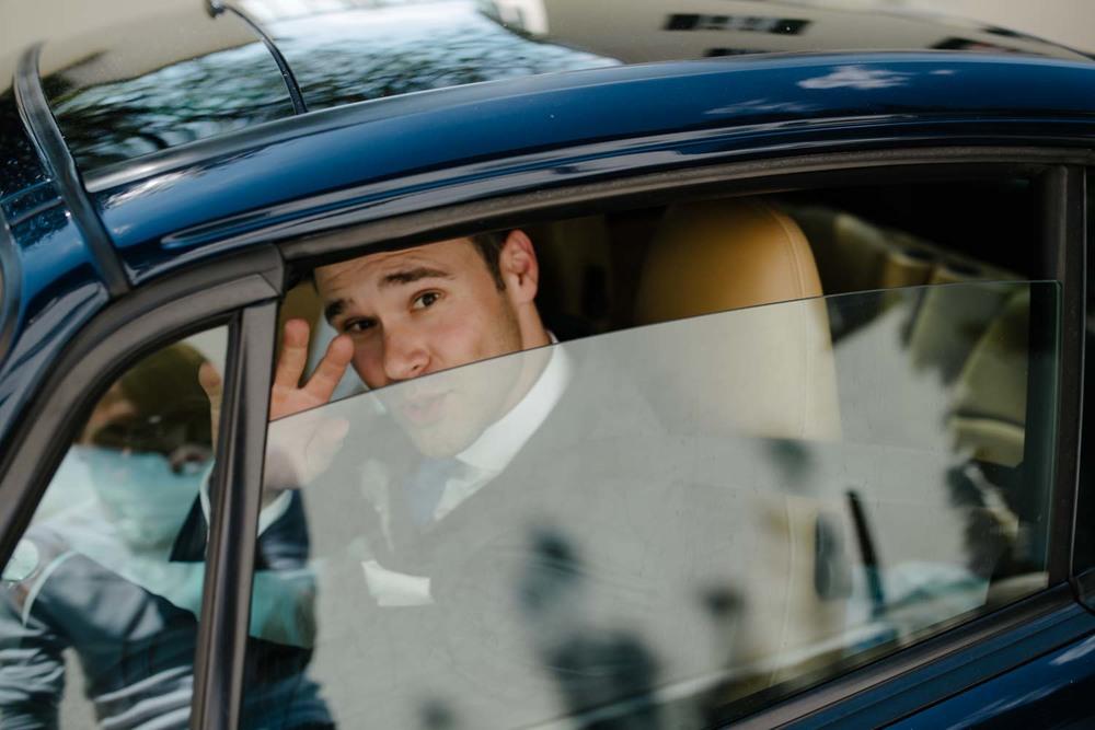 Bräutigam winkt beim vorbeifahren Hochzeitsauto Hochzeit Rostocker Fotograf in Augsburg
