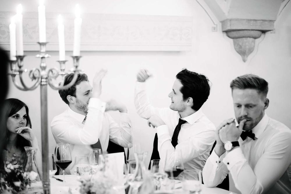 Herren in weissen Hemden albern am Tisch beim Abendessen Hochzeit Rostocker Fotograf in Augsburg