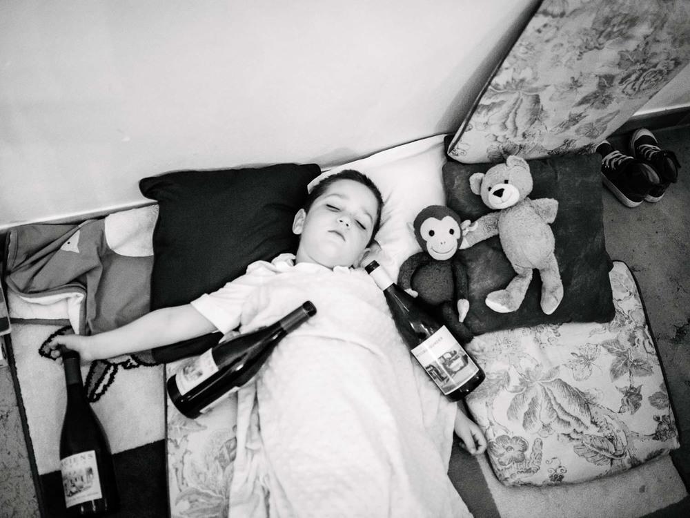 schlafendes Kind mit vielen Weinflaschen Hochzeit Rostocker Fotograf in Augsburg