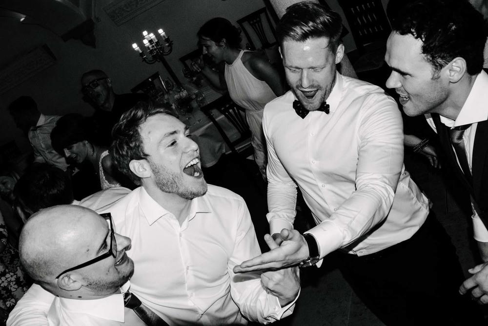 Tanzende Herren in weissem Hemd und Fliege rocken die Tanzfläche Hochzeit Rostocker Fotograf in Augsburg