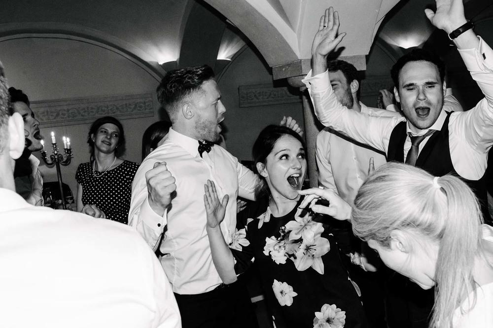 Dame im Cocktailkleid  und Herren in Anzug und Fliege beim Feiern  HerrenHochzeit Rostocker Fotograf in Augsburg