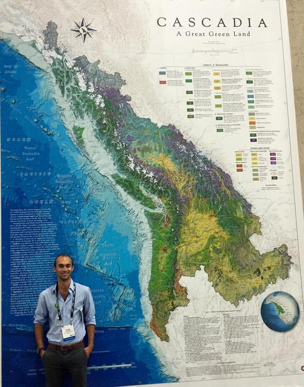 Cody Camarata stands in front of a massive blowup of David McCloskey's new Cascadia Bioregion map - 'Cascadia a Great Green Land'. In all more than 15,000 people had the chance to see the map at this years 2015 ESRI User Conference at UC San Diego, July 20th-24th. Awesome photo by Alex Philip @BigDataAlex on twitter!