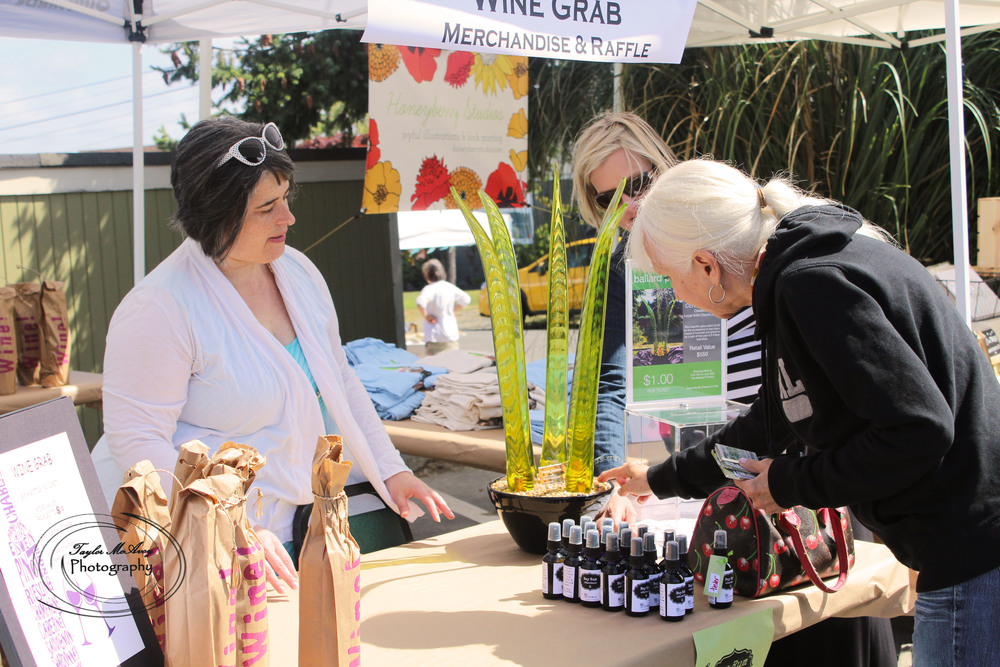 Dahlia Cohen chats with customers about the Wine Grab as they sign up for a raffle for a piece of glass art by Dayne Lopez. The Wine Grab features volunteer donated wine organized in Red or White and the rest is a mystery until unwraped.