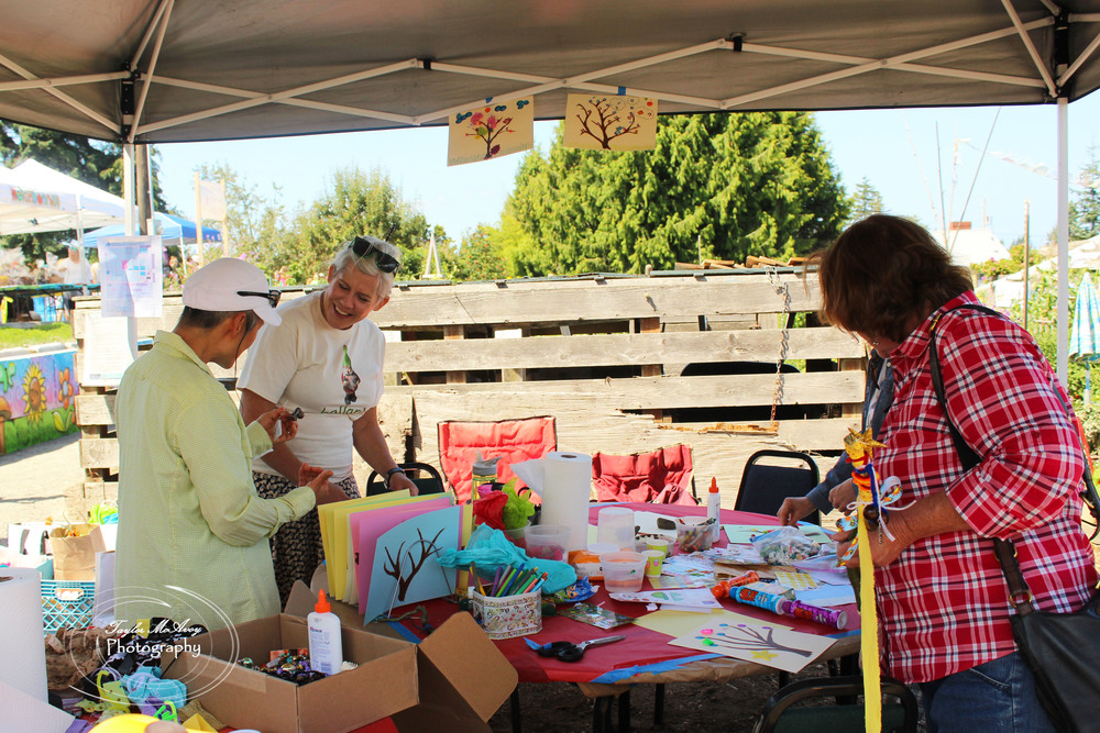 Korinne Kuchling (middle left) helps fellow volunteers set up the kids booth promoting hands on arts and crafts. Korinne and her husband have been volunteering at the P-Patch for about 7 years.