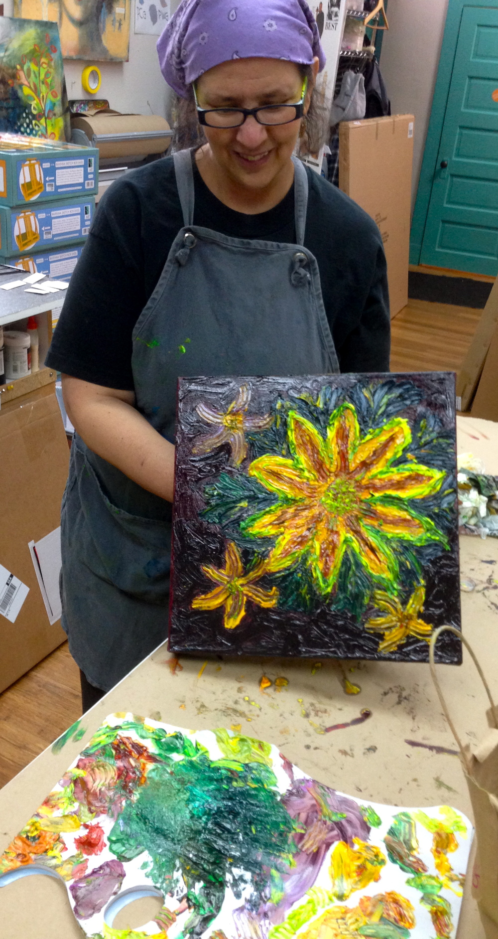 Paula at the ARTspot studio creating a painting with water soluble oil paints and applies solely with her (gloved) fingers.