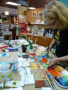 Local artist and owner of ARTspot Tracy Felix demonstrates painting techniques on 5x5 inch canvases in her shop's studio. She hosted a 25 Day Creativity Challenge for other artists, challenging them to create 25 5x5 inch original pieces in 25 days. Photo by: Laura Daniali