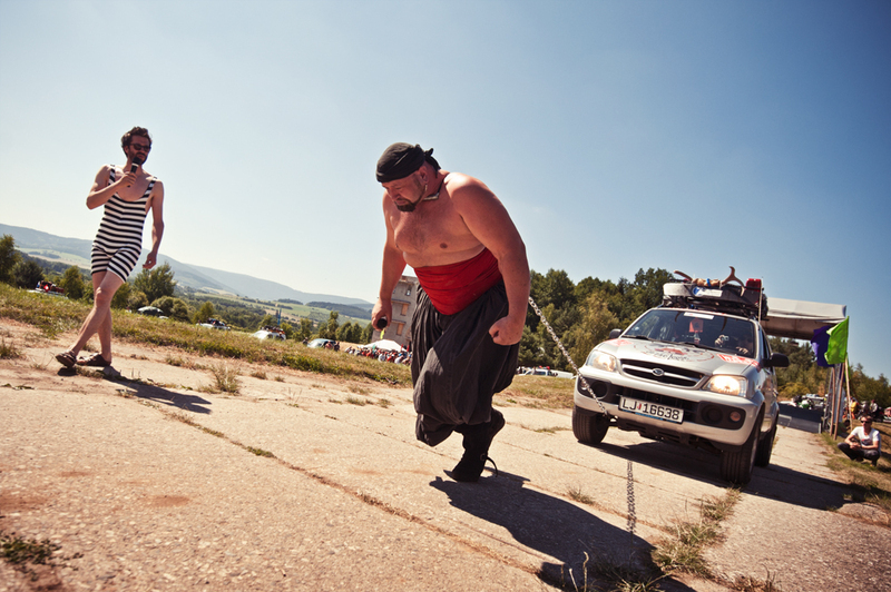 The strongman drags a car by his neck