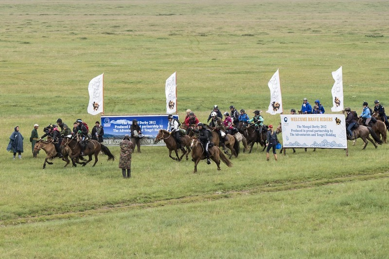 Riders cross the start line of the Mongol Derby 2012: