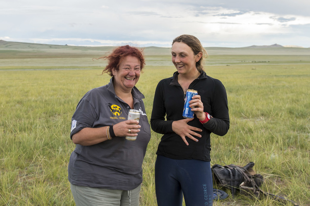 Winner Lara Prior-Palmer is given a congratulatory beer by race referee Maggie Pattinson at the end of the Mongol Derby, 10th Aug 2013.