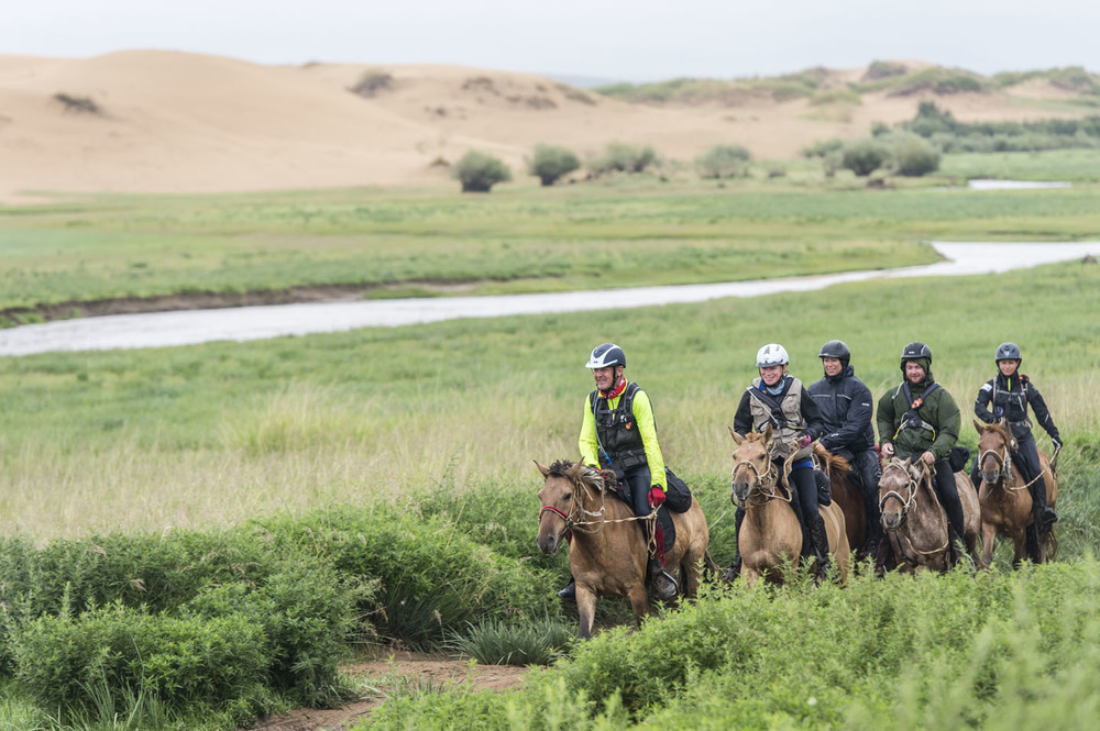 Anthony Ward-Thomas leads a string of riders into horse station 3, 5th Aug 2013. They are riding past a huge line of sand dunes which run for 200km through central Mongolia