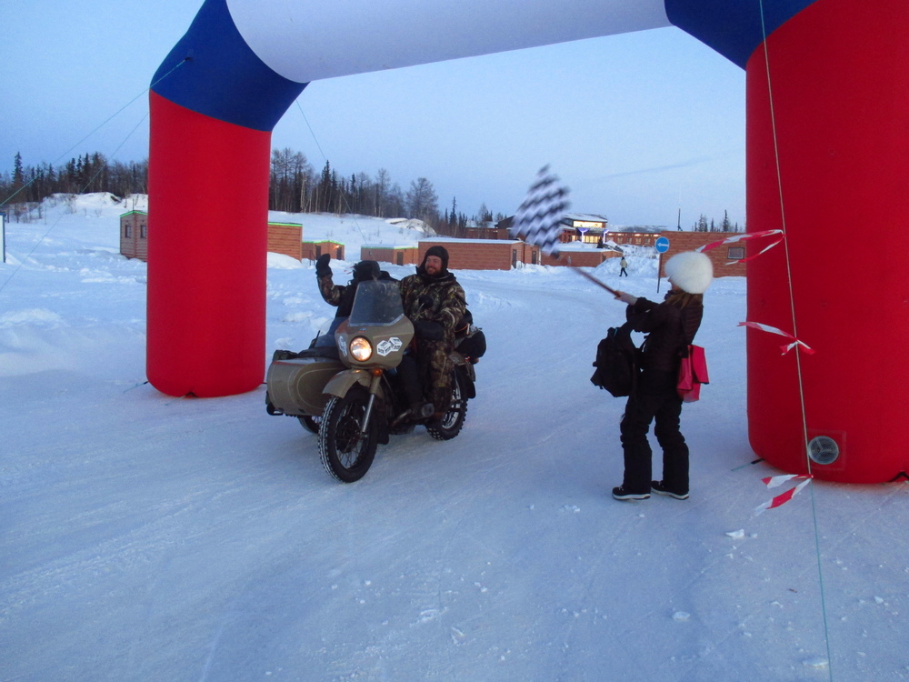 Mo drives Sam over the finish line after an epic journey from Irbit to the Arctic. Ice Run Chief Katy flies the chequered flag for them